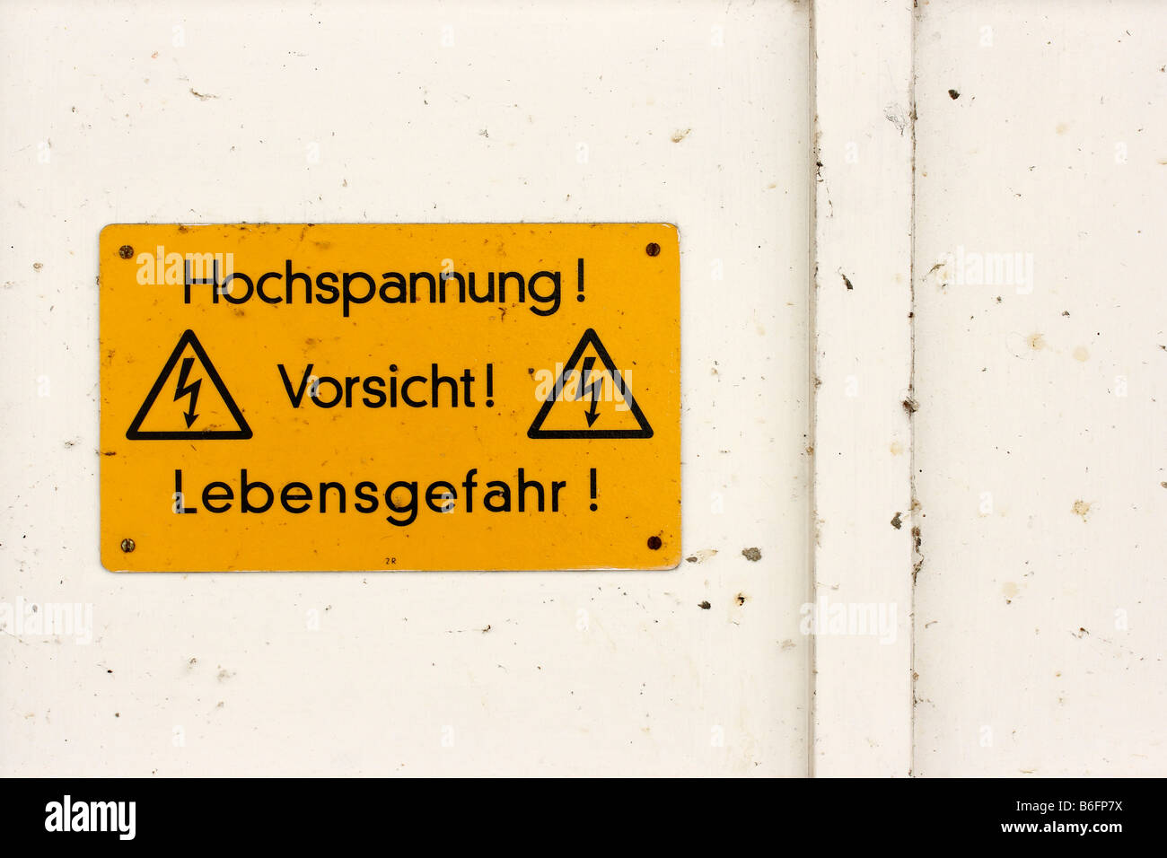 High tension! Caution! Danger! Instruction and warning sign on a house wall - Stock Image