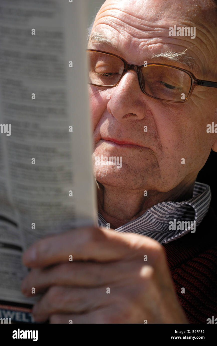 4f600535acbd Old man wearing glasses and reading a newspaper with a serious expression