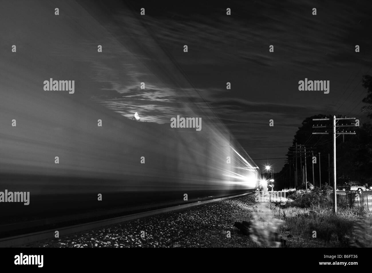 A westbound train speeding through town at night - Stock Image