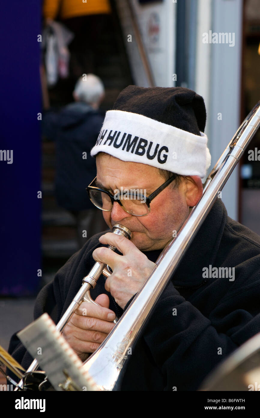 UK Cheshire Chester Eastgate Street Christmas Whitchurch Band player in Bah Humbug Hat - Stock Image