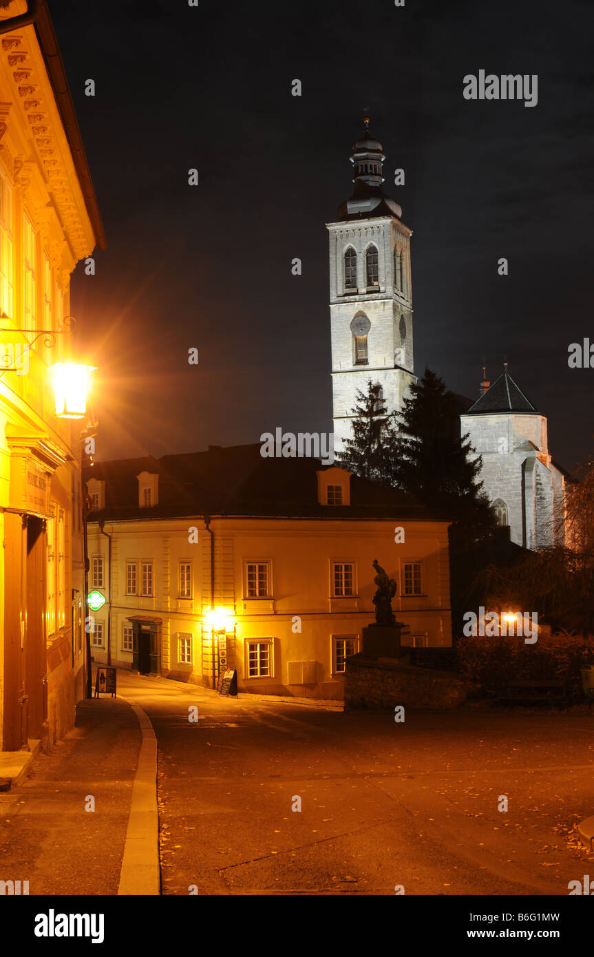 Barborská street in Kutná Hora, Czech Republic. Night view with illuminated st. James Church in the background. - Stock Image