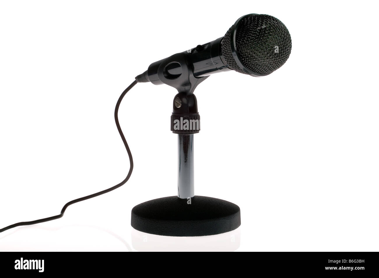 Black microphone with lead on a stand isolated on a white background - Stock Image