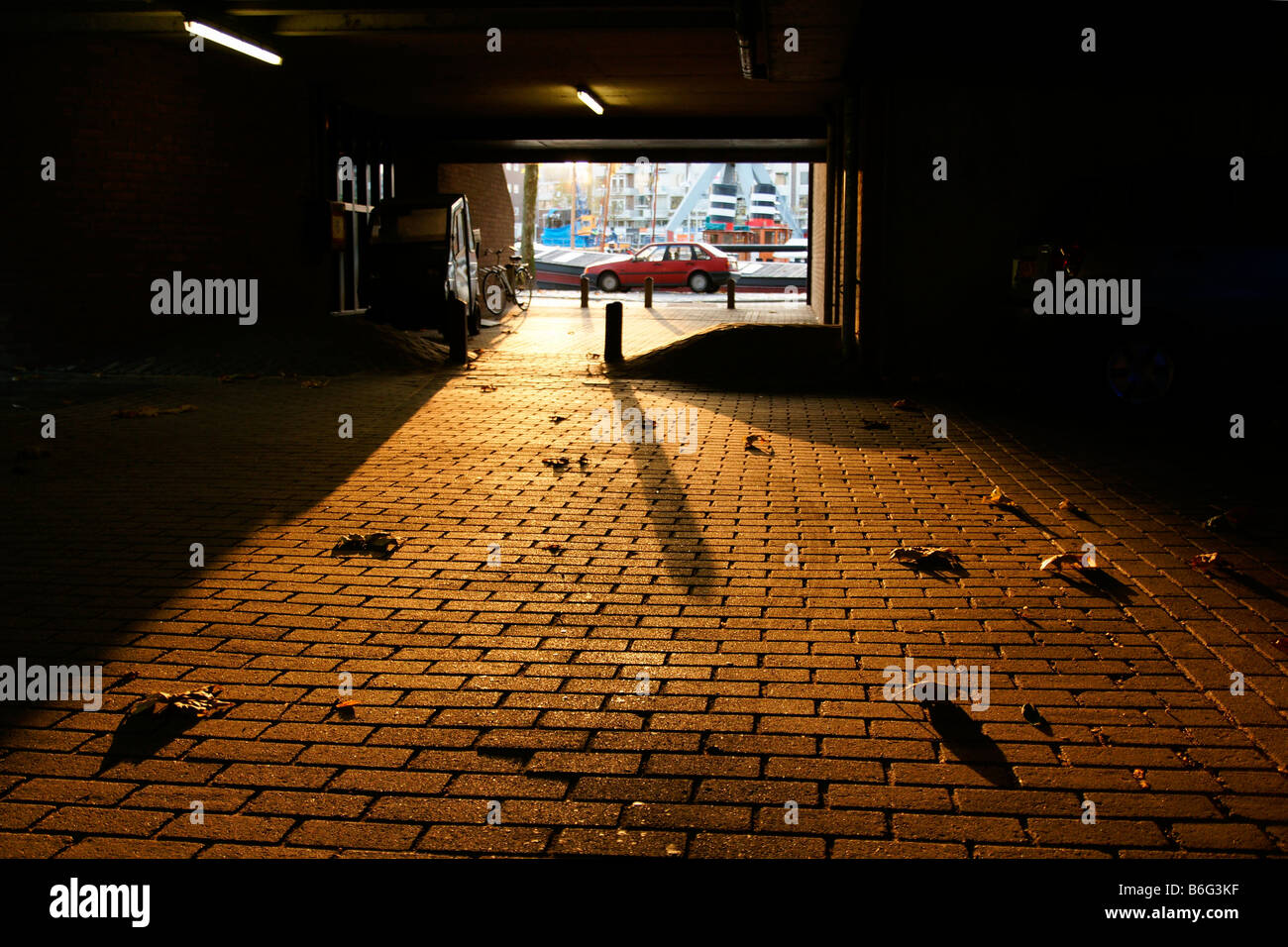 Underway passage garage park lit by evening sun under apartment house in Rotterdam Netherlands - Stock Image