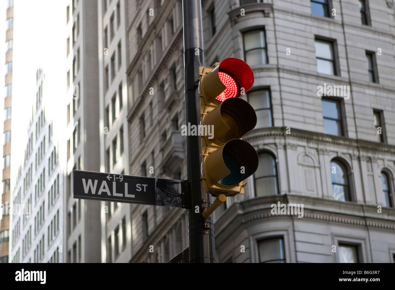 A Wall Street street sign is seen next to a red traffic light in New York, NY. - Stock Image