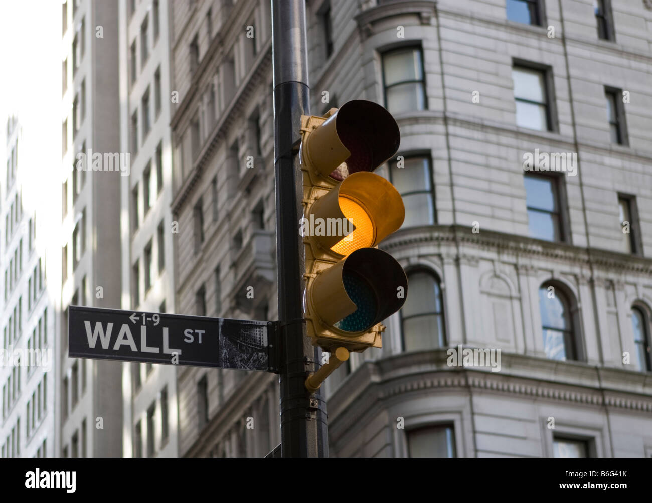 A Wall Street street sign is seen next to an amber traffic light in New York, NY. - Stock Image