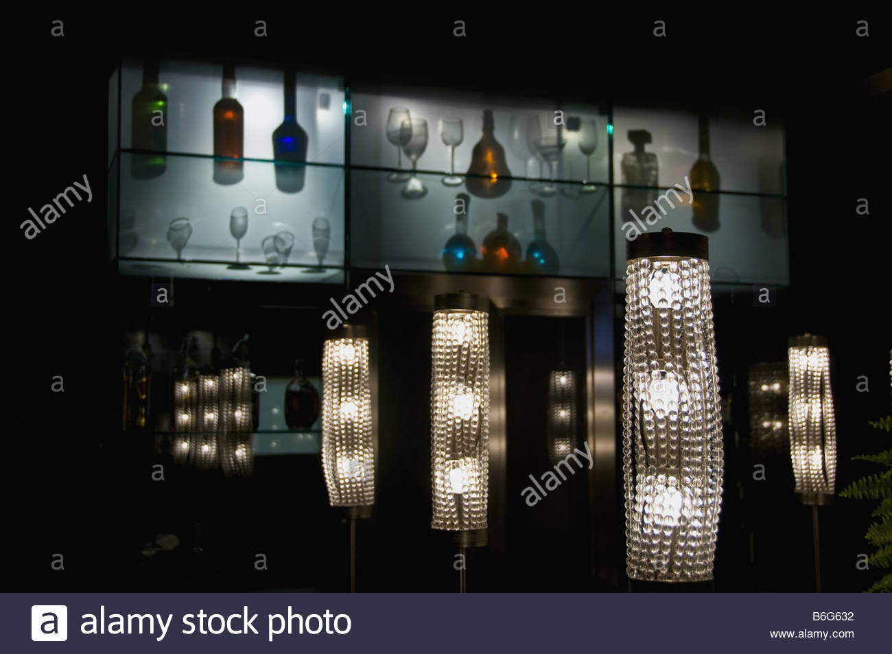 Design lamps and illumination effects with bottles and glasses. - Stock Image
