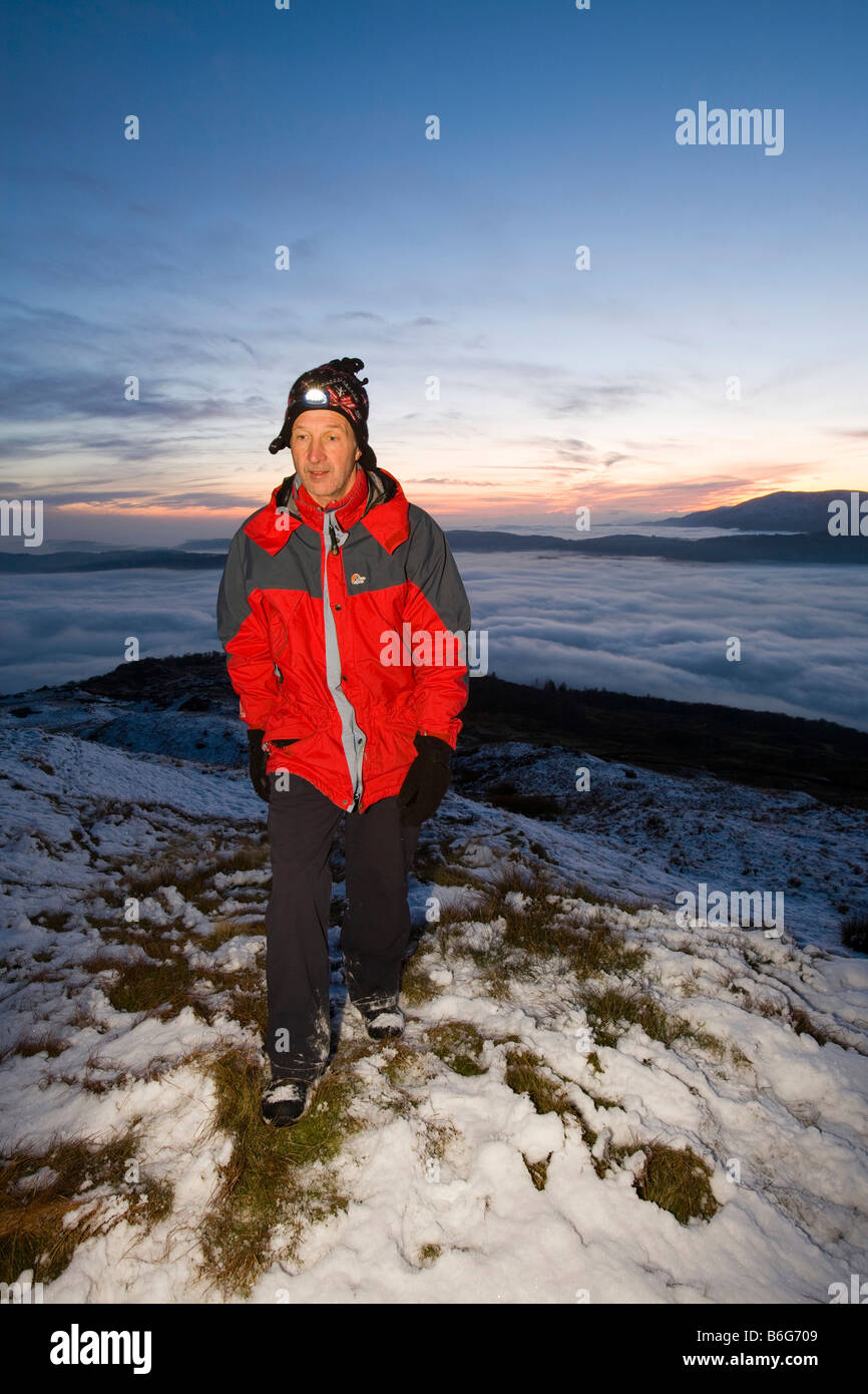 A walker on Wansfell Pike in the Lake District UK with valley mist below - Stock Image