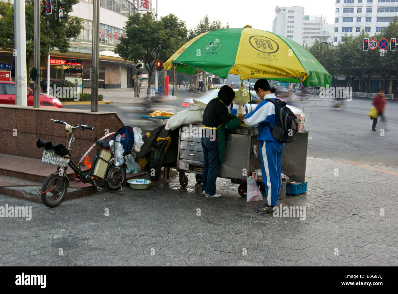 School boy buying breakfast from roadside food vendor stall on downtown street corner with busy traffic in motion Stock Photo