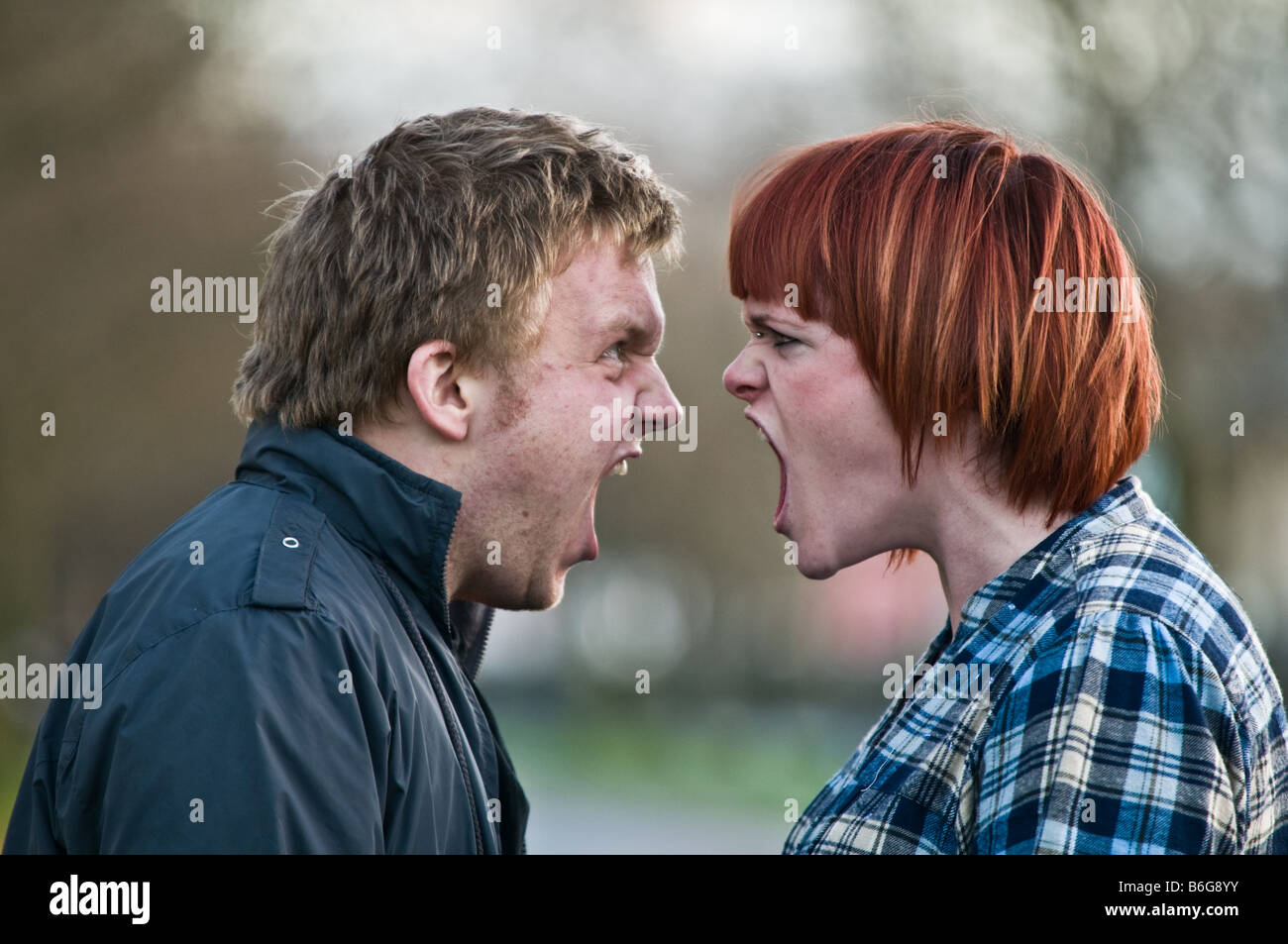 young british english couple man and woman having a full on blazing row argument shouting at each other face to - Stock Image
