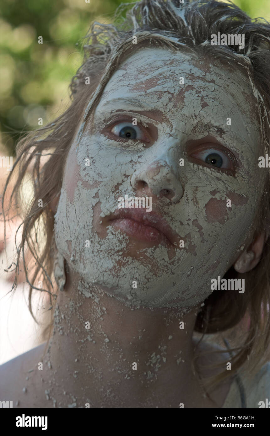 Portrait of Wide Eyed Staring Woman Girl with Mud face mask - Stock Image