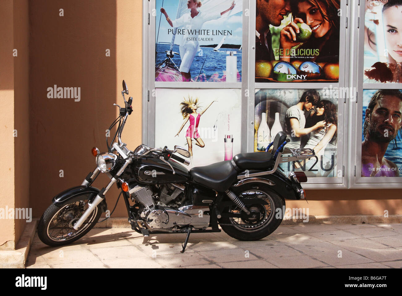 Old Yamaha bike parked next to some advertising boards in bright sun in Palma Nova, Majorca. - Stock Image