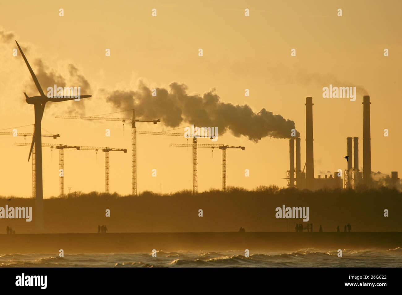 Wind turbine cranes industrial factory chimneys pink sky smoke plume pollution sky Hoek van Holland Netherlands - Stock Image