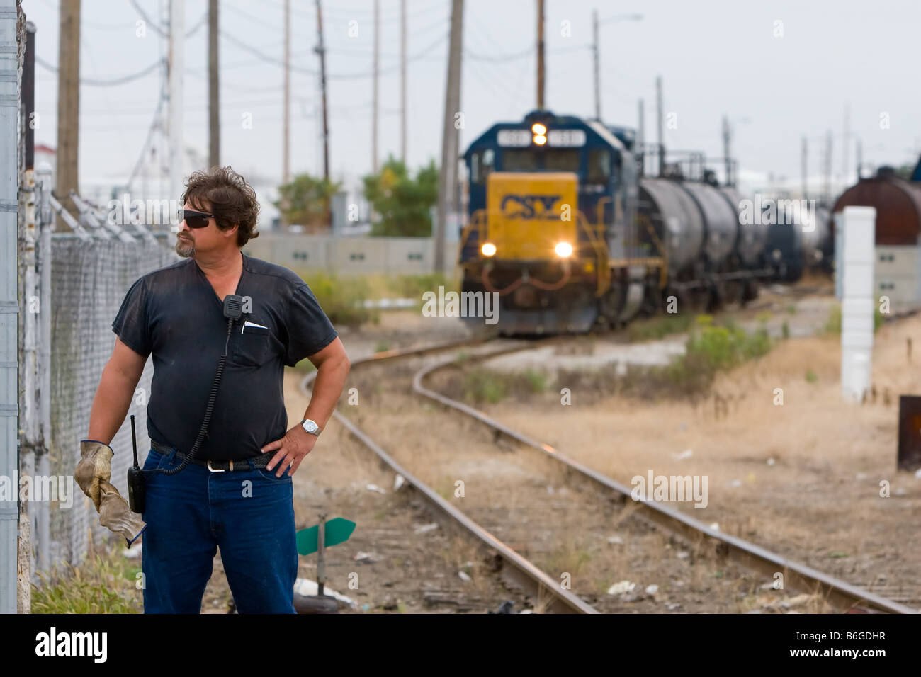 A conductor on a CSX freight train stands at a road crossing