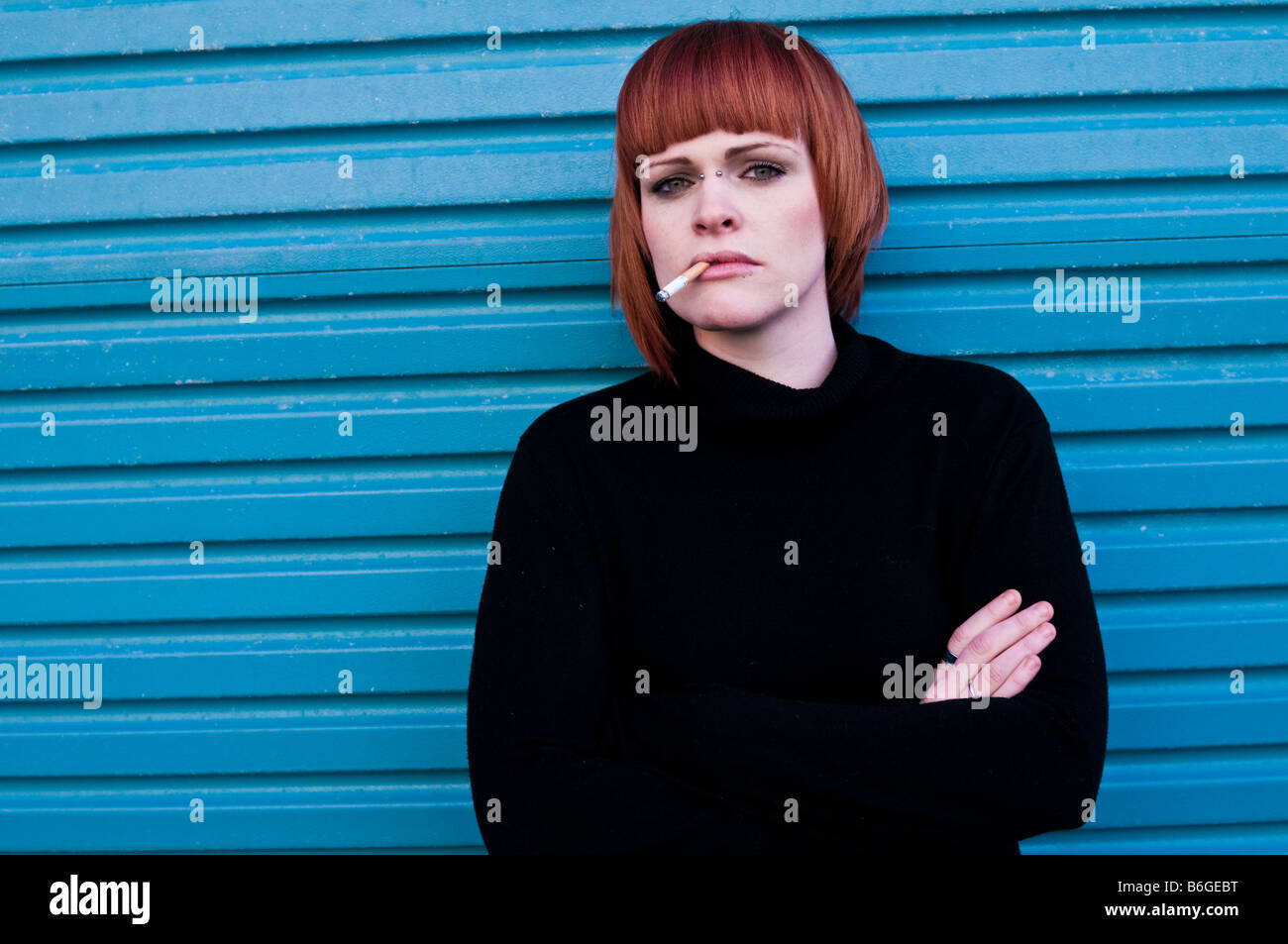 Young red haired girl woman with a cigarette in her mouth arms crossed in front of blue garage doors, outside, UK - Stock Image