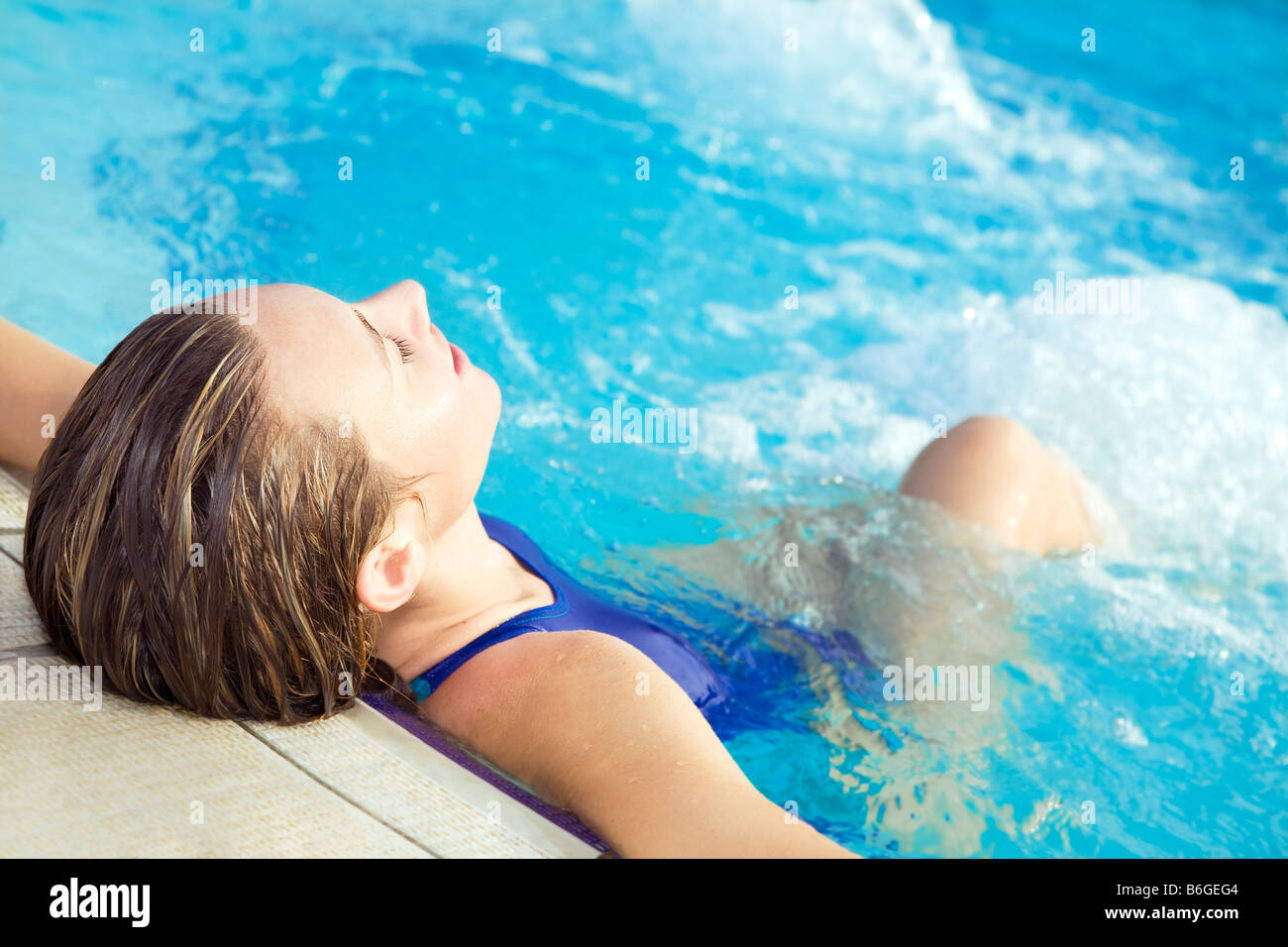 Portrait of young woman sitting in swimming pool Stock Photo