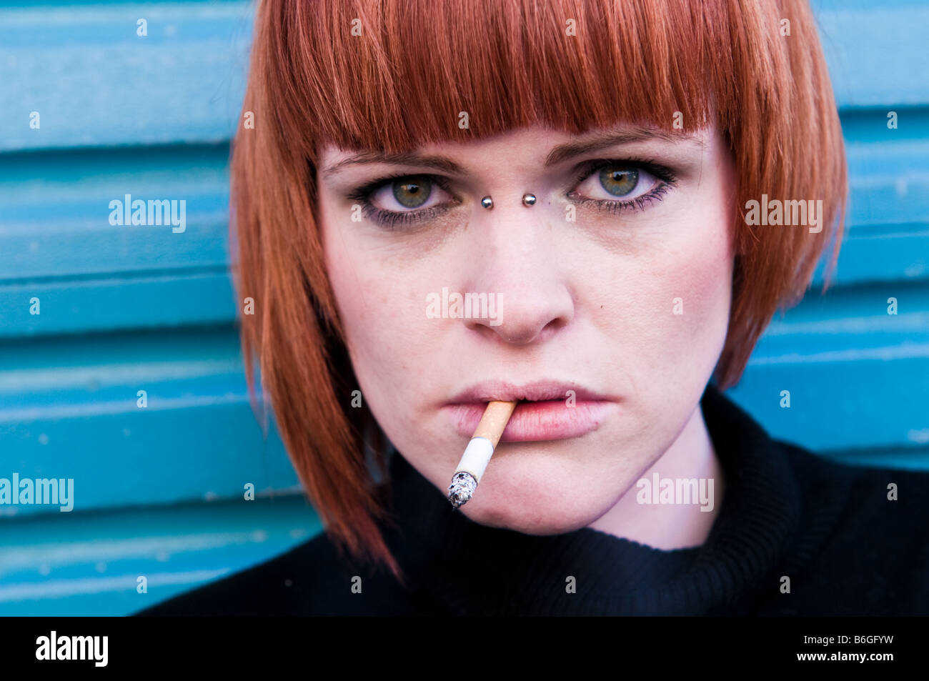 Young red haired irish girl woman with a cigarette in her mouth, a piercing in the bridge of her nose looking moody Stock Photo
