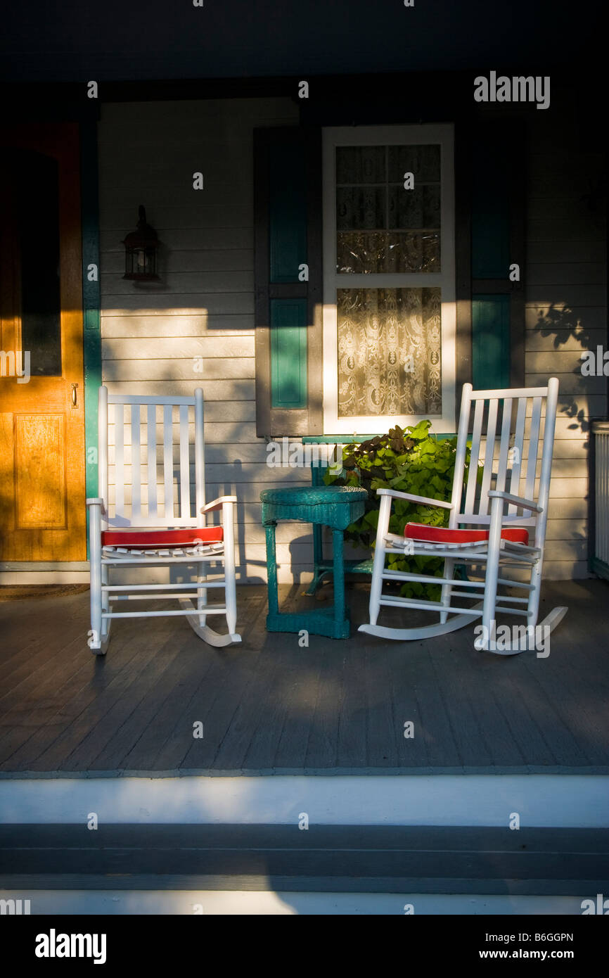 Evening Sun On A Quaint Victorian Porch With Two Rocking Chairs And A  Window With Lace Curtains.