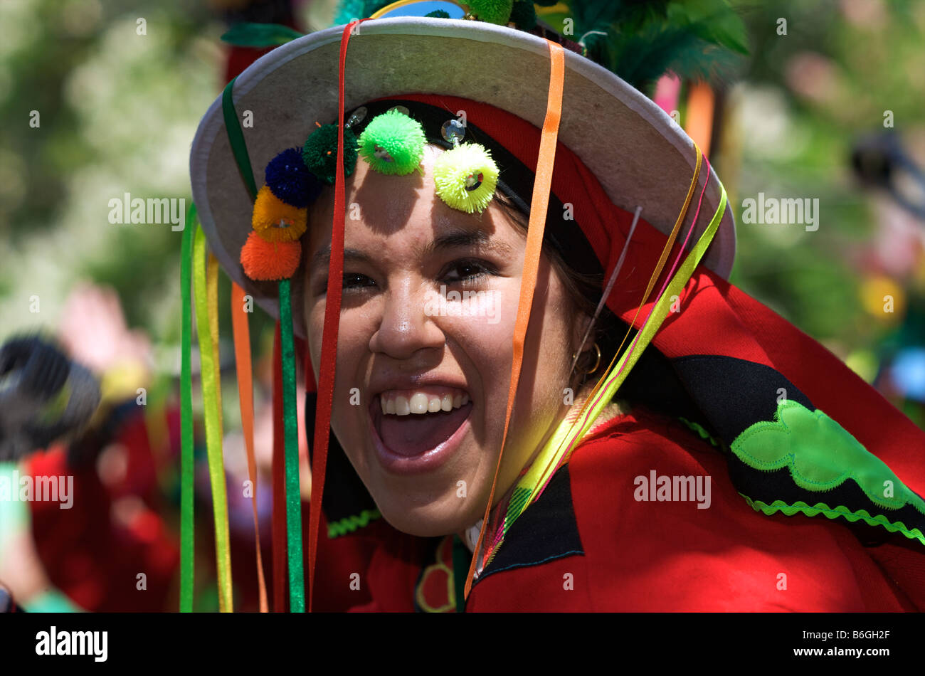 Laughing Girl in red costume with hat and ribbons - Stock Image