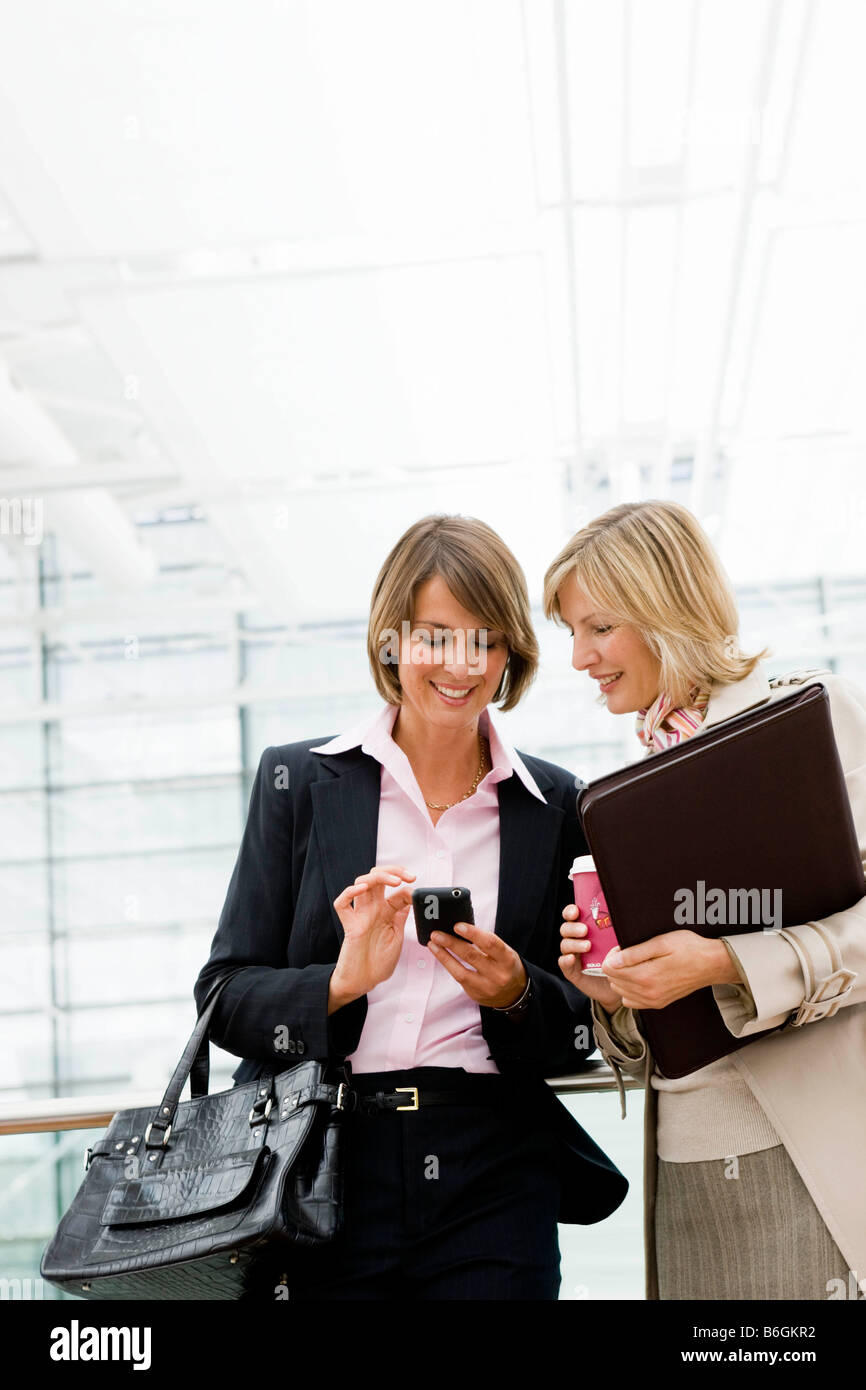 Two women looking at device - Stock Image