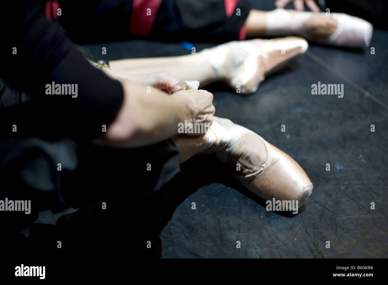 a ballerina ties her pointe shoes during a rehersal of the English National Ballet s sleeping beauty - Stock Image