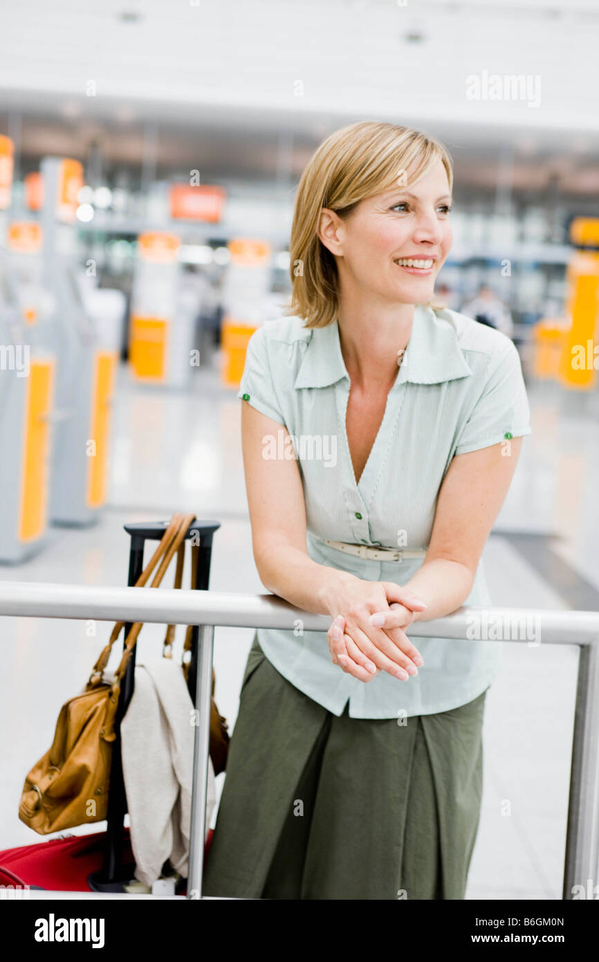 Woman leaning on rail waiting - Stock Image