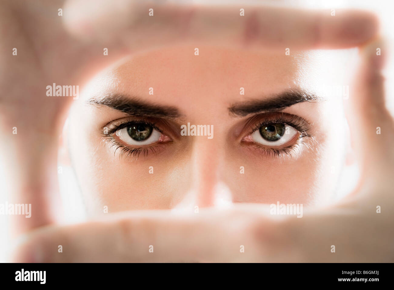 Portrait of eyes looking through fingers frame - Stock Image
