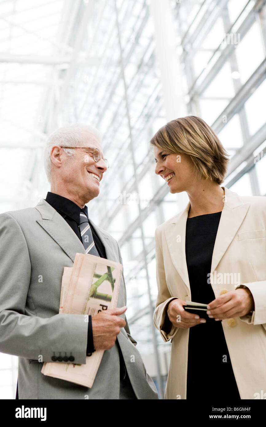 Older man talking to younger woman - Stock Image