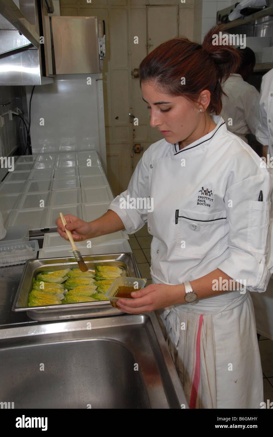 A young girl chef in a busy kitchen at the Cafe de la Cloche in rue de la Charité, Lyon,France. - Stock Image