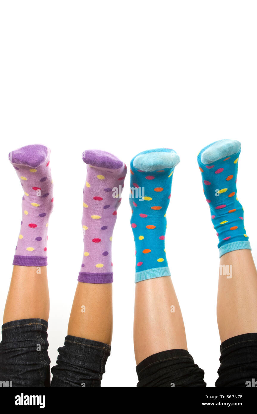 Vertical close up portrait of two pairs of feet in spotty socks in the air against a white background Stock Photo