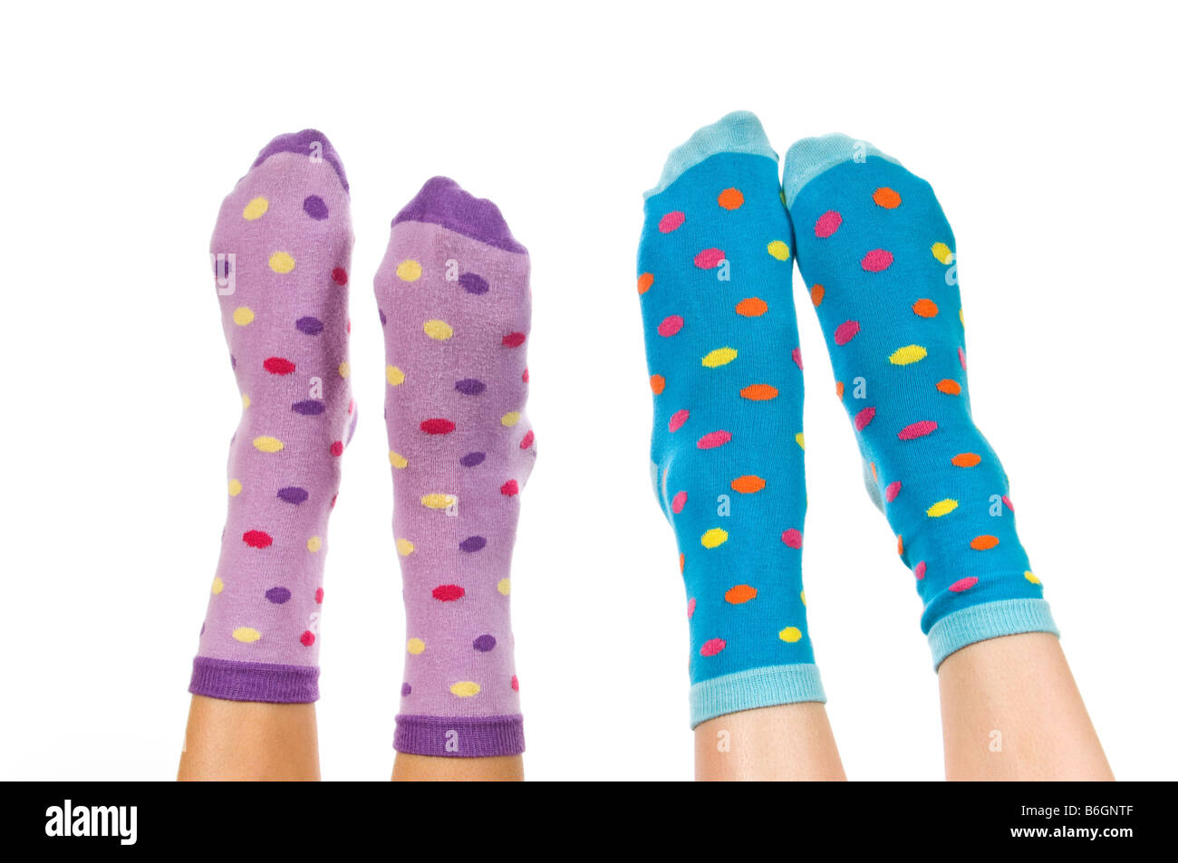 Horizontal close up portrait of two pairs of pointed feet wearing spotty socks in the air against a white background - Stock Image