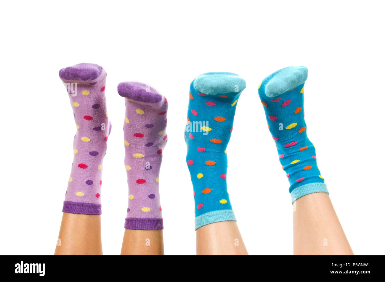Horizontal close up portrait of two pairs of feet wearing spotty socks in the air against a white background - Stock Image