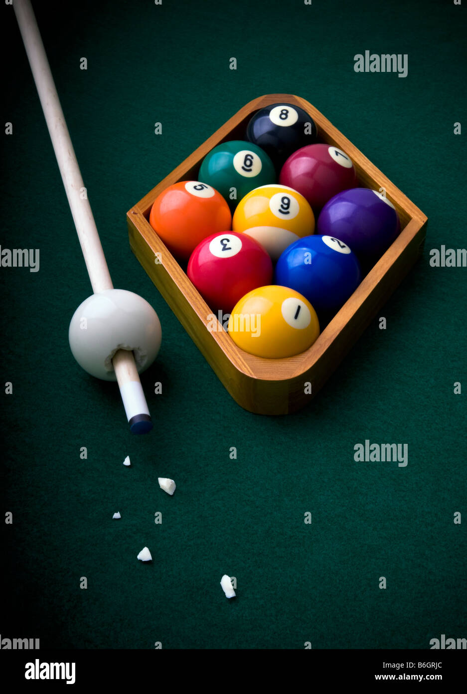 Billiard, pool balls arranged in a nine ball rack on a green felt table with a surrealistic view of the cue ball - Stock Image