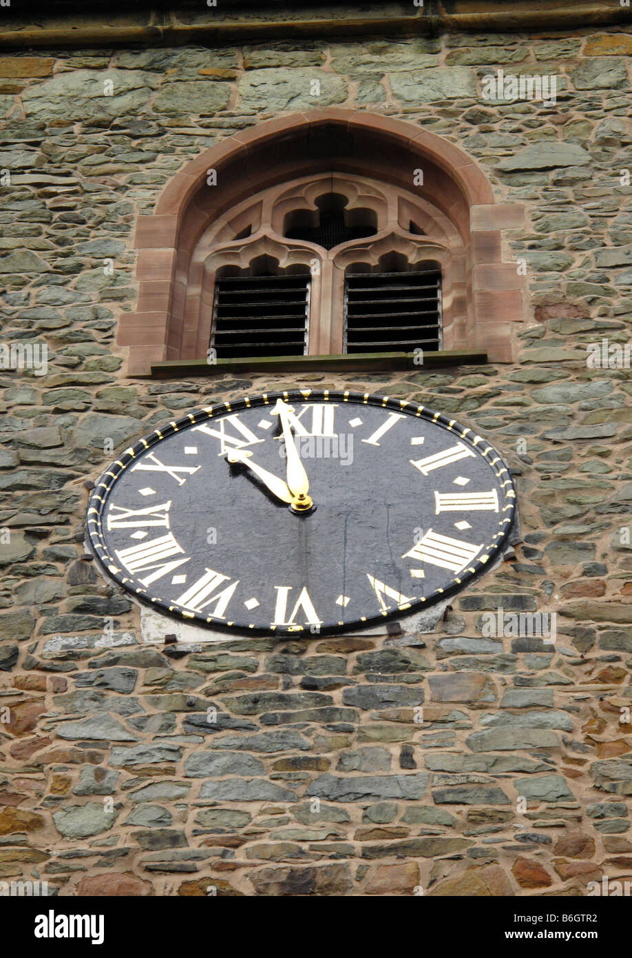 Metal clock face showing 10.59 with roman numerals on stone church clock tower with louvered stone mullion window - Stock Image
