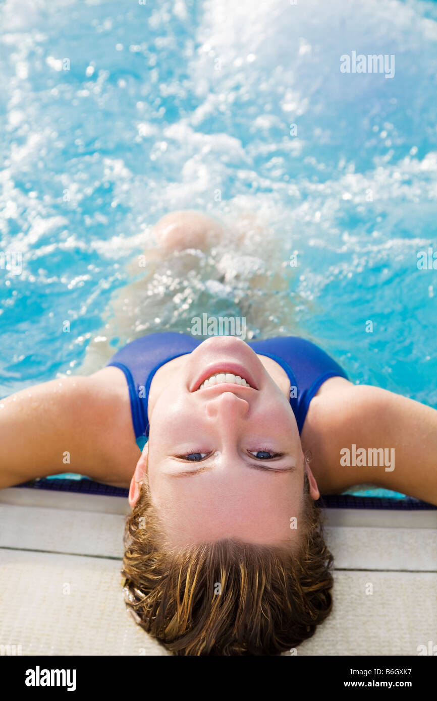 Portrait of young woman sitting in swimming pool rear view Stock Photo