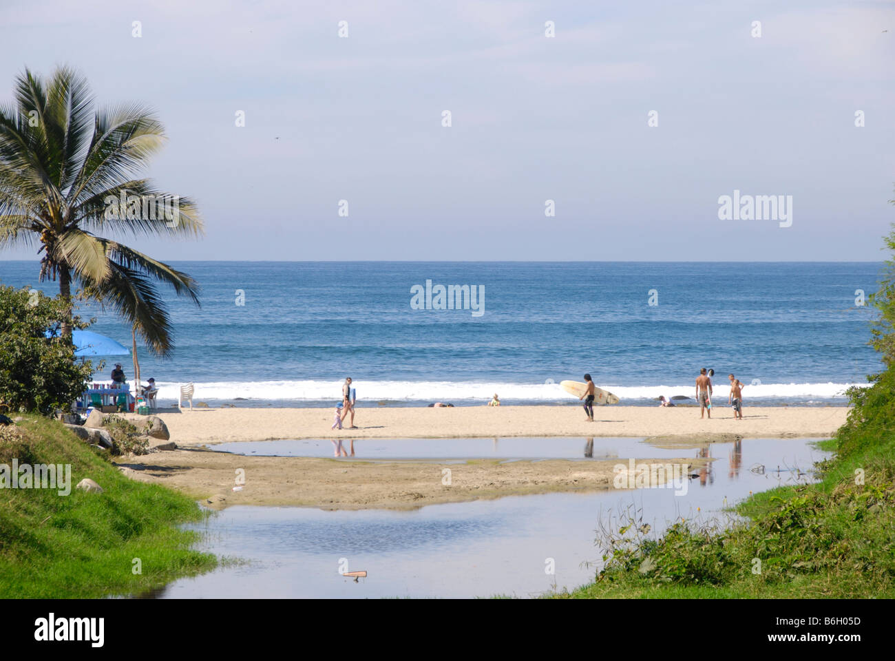 view of lagoon with tropical vegetation opening onto bright variegated beach scene on a sunny day in Sayulita, Mexico - Stock Image