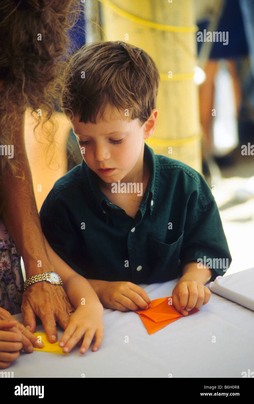 Young boy gets guidance from adult as he makes folded paper art project. - Stock Image