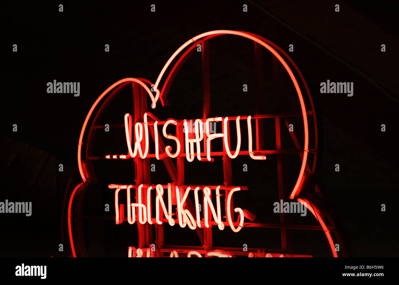 A 'Wishful Thinking' sign in red neon at night. - Stock Image