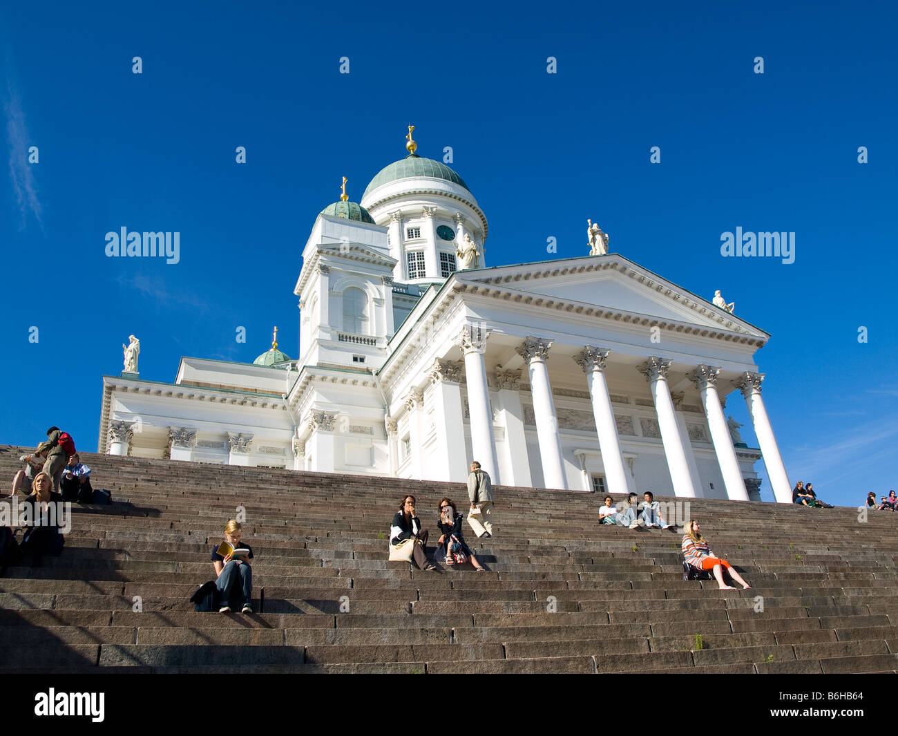 Sitting on the steps of Tuomiokirkko, one of Helsinki, Finland's most recognizable landmarks. - Stock Image