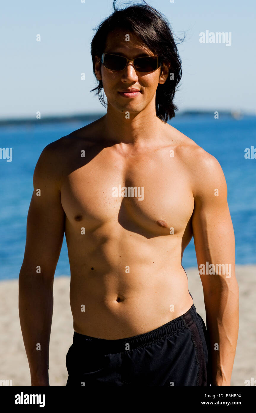 muscular-asian-male-on-beach-on-summer-day-B6HB9X.jpg