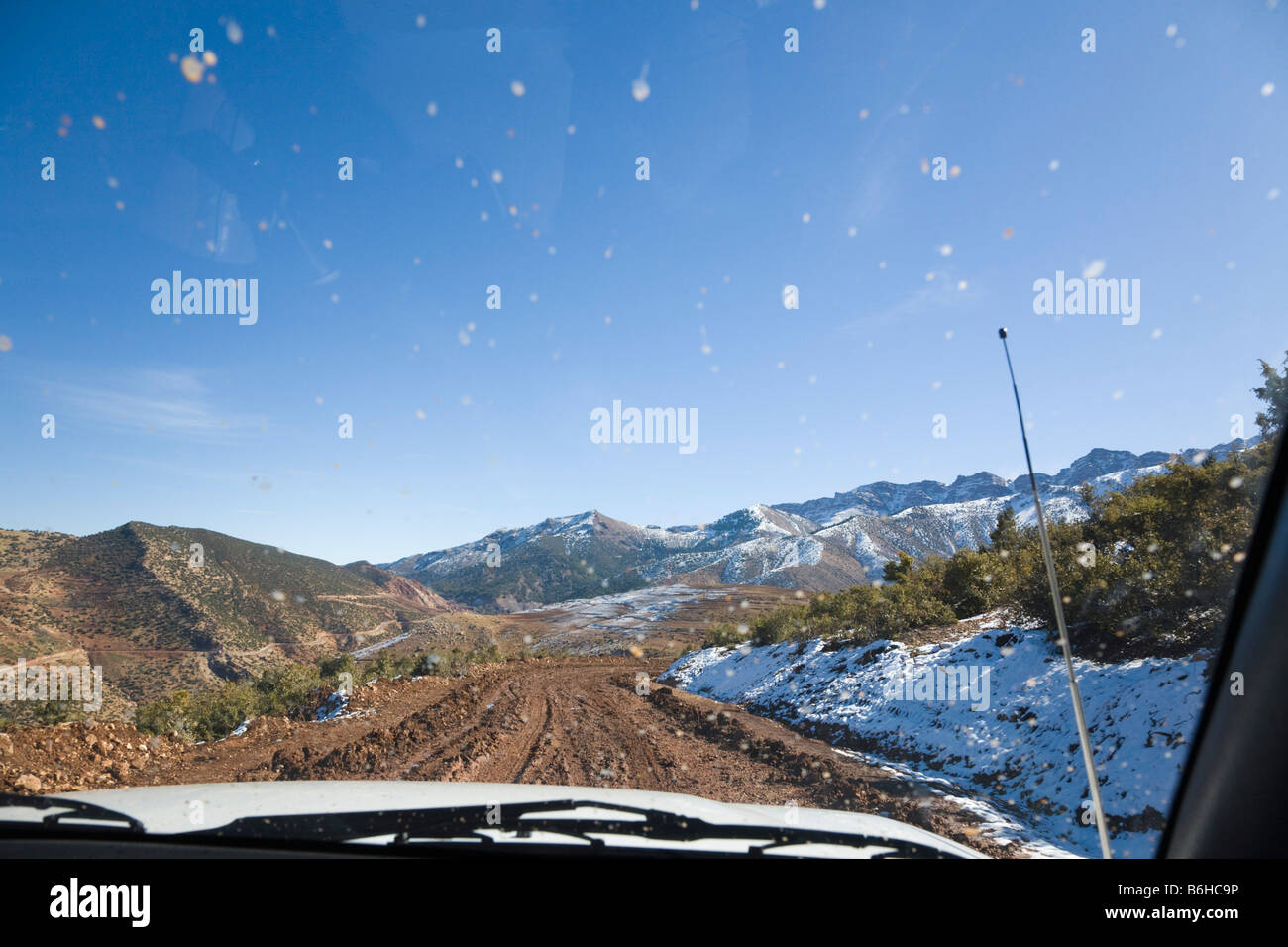 View through muddy windscreen of 4x4 offroad safari vehicle on dirt road in High Atlas Mountains in winter. Asni - Stock Image