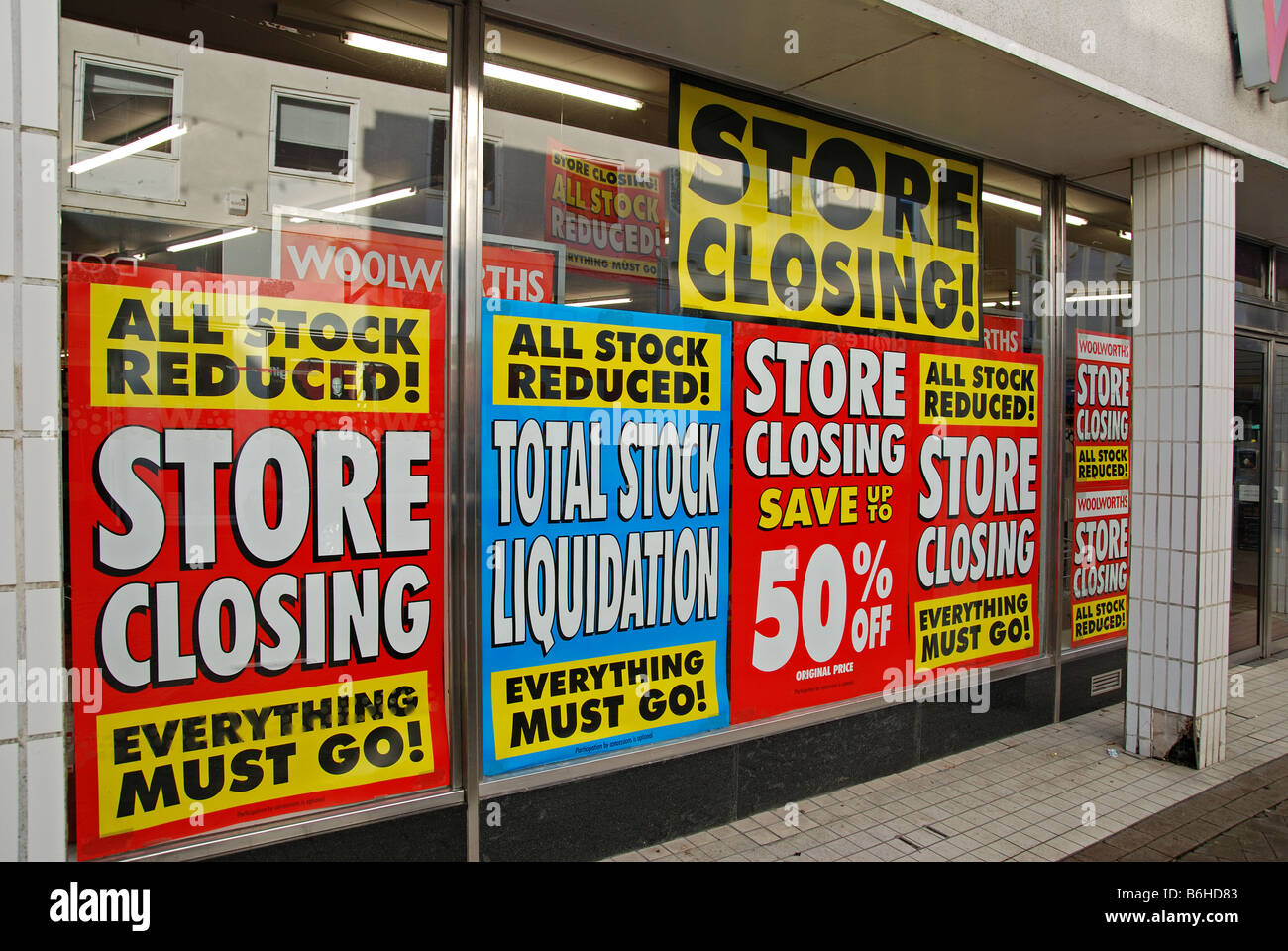 store closing down posters in the window of a woolworths store,england,uk - Stock Image