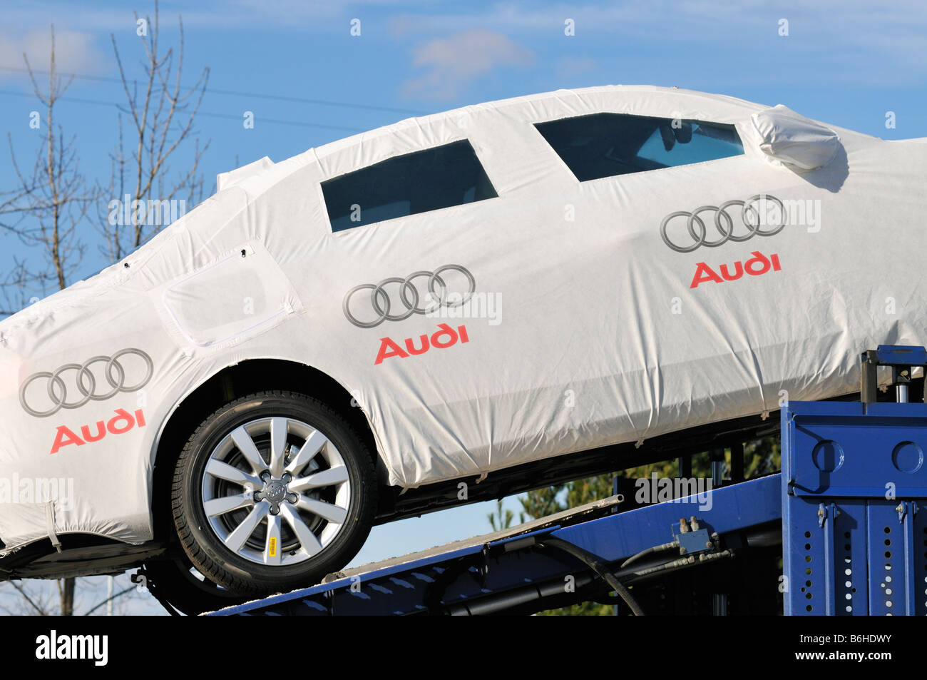 Covered Audi car on car carrier for delivery - Stock Image