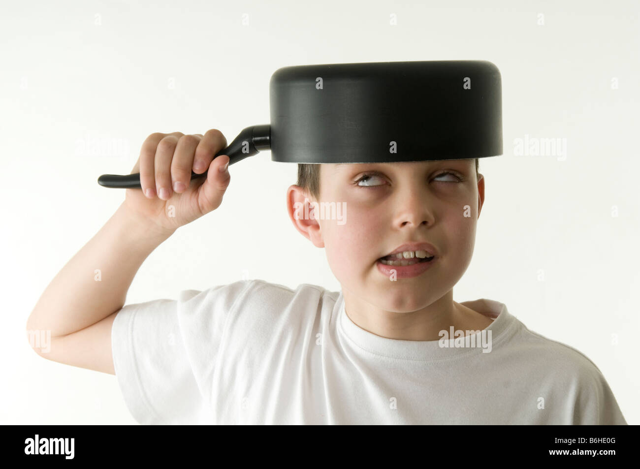 funny silly boy child messing about fun happy saucepan on head sauce pan with face stupid acting comedian comedy - Stock Image