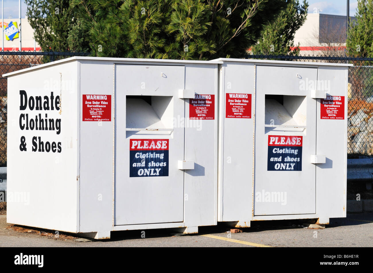 2 two donate clothing bins outside in parking lot - Stock Image