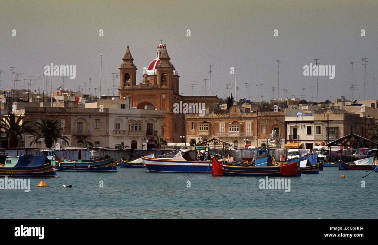 Traditional Maltese fishing boats called Luzzus moored in Marsaxlokk harbour - Stock Image