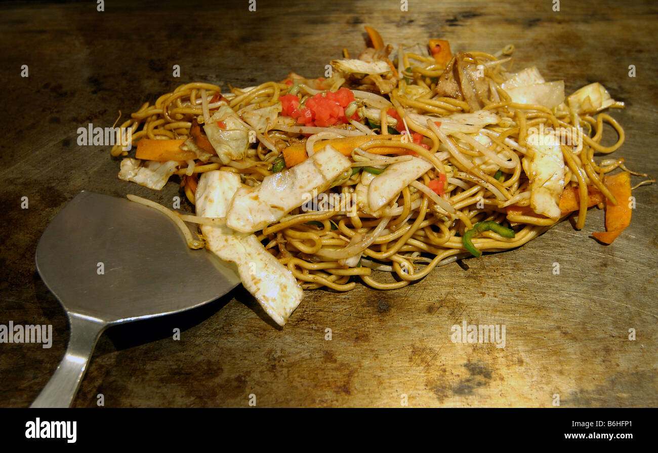 Japanese fried noodles cooking on a hot plate in a Japanese restaurant. YAKISOBA - Stock Image