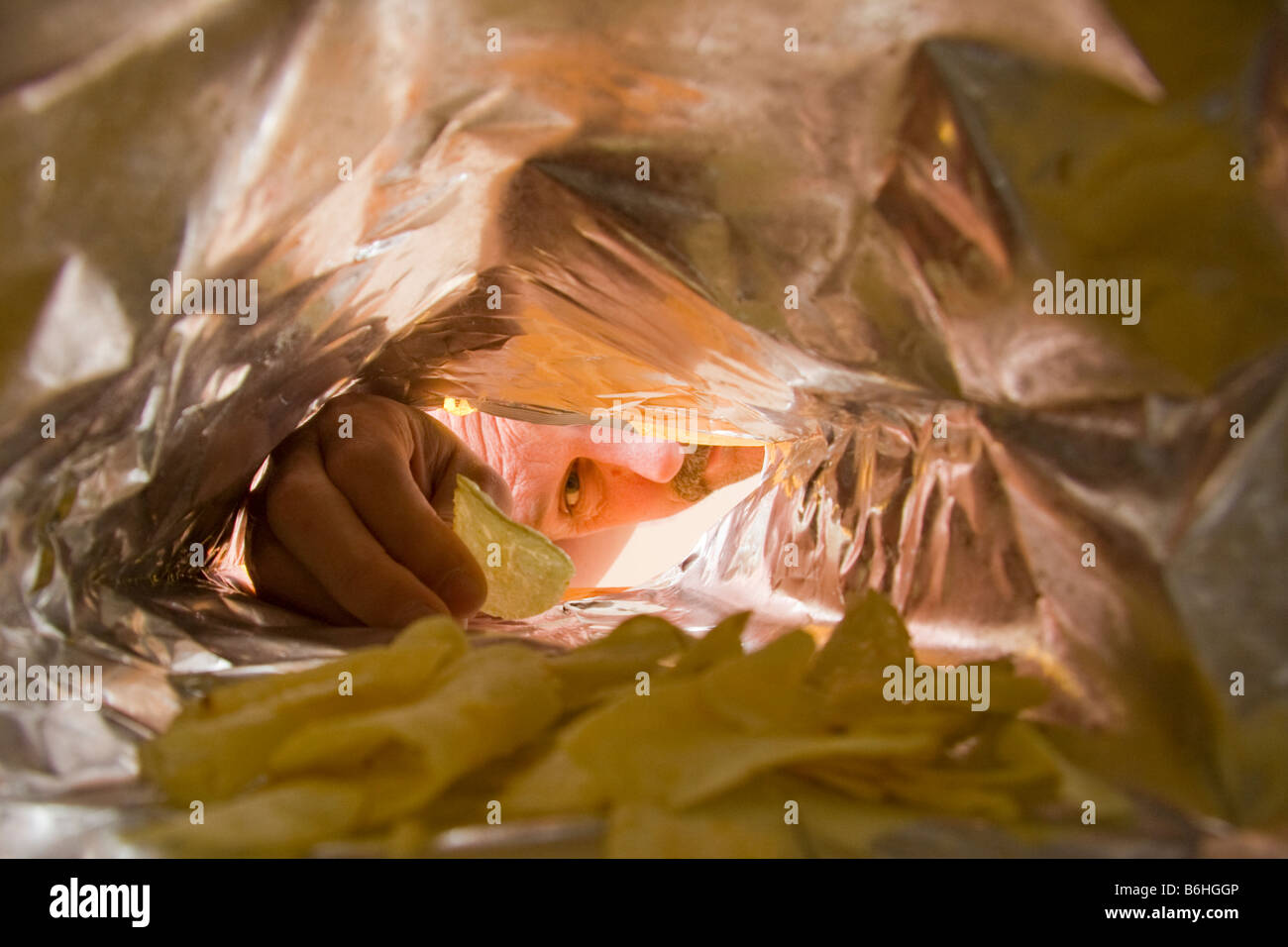 Reaching into a bag for some potato chips - Stock Image