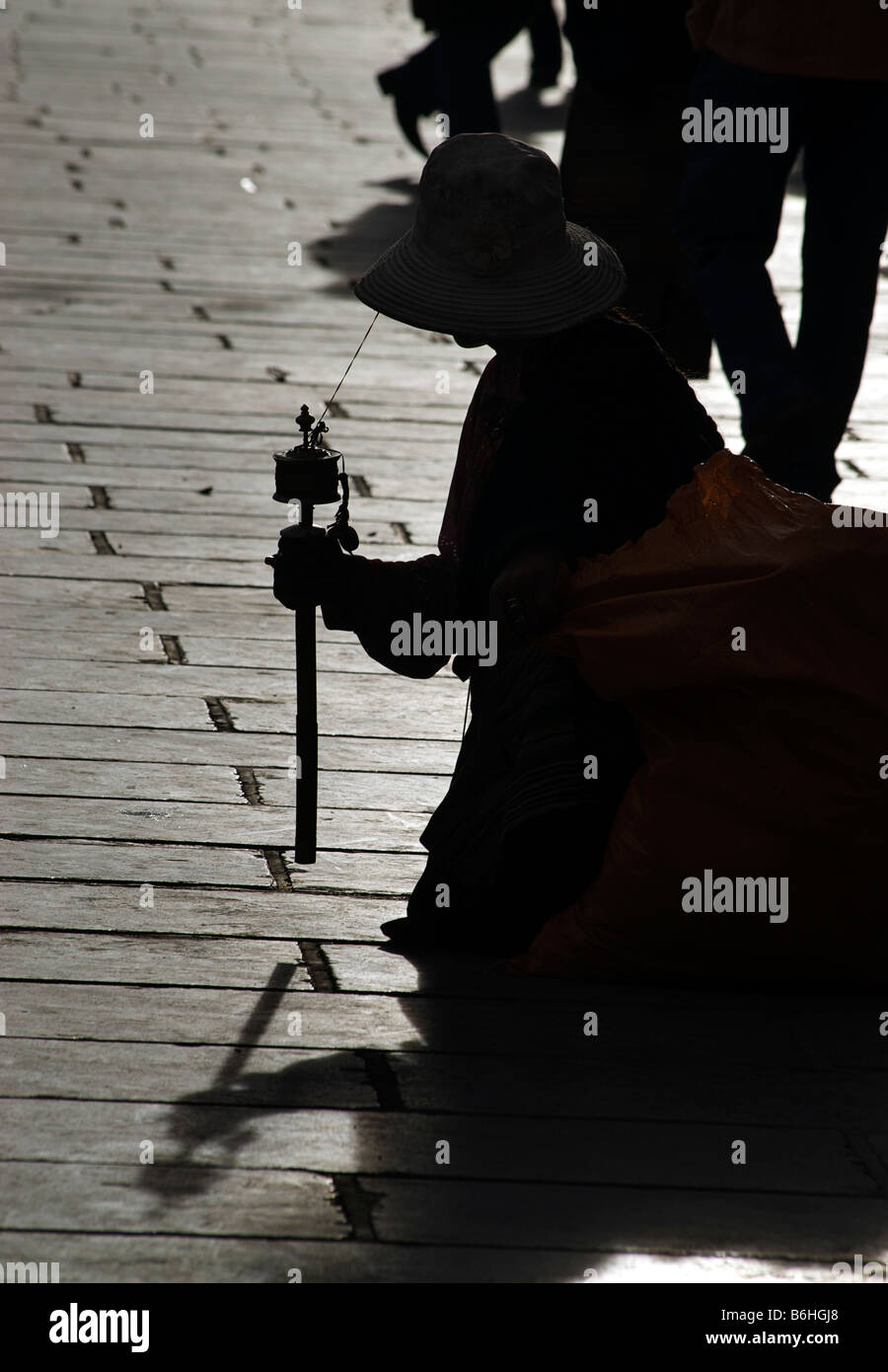 Silhouetted shape of a Tibetan pilgrim in Barkor Square, Lhasa, Tibet - Stock Image