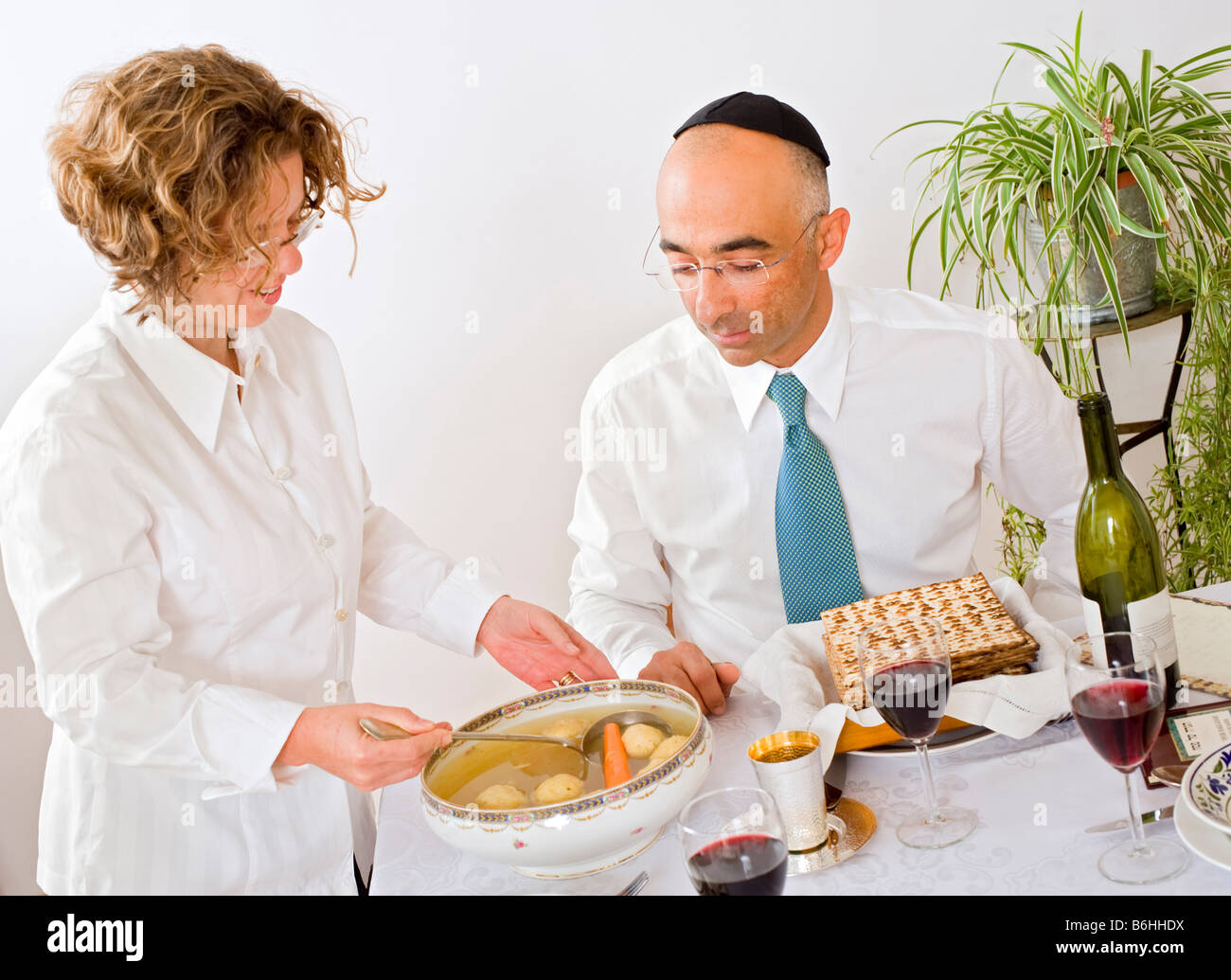 mother serving Kneidel soup at Passover family Seder - Stock Image