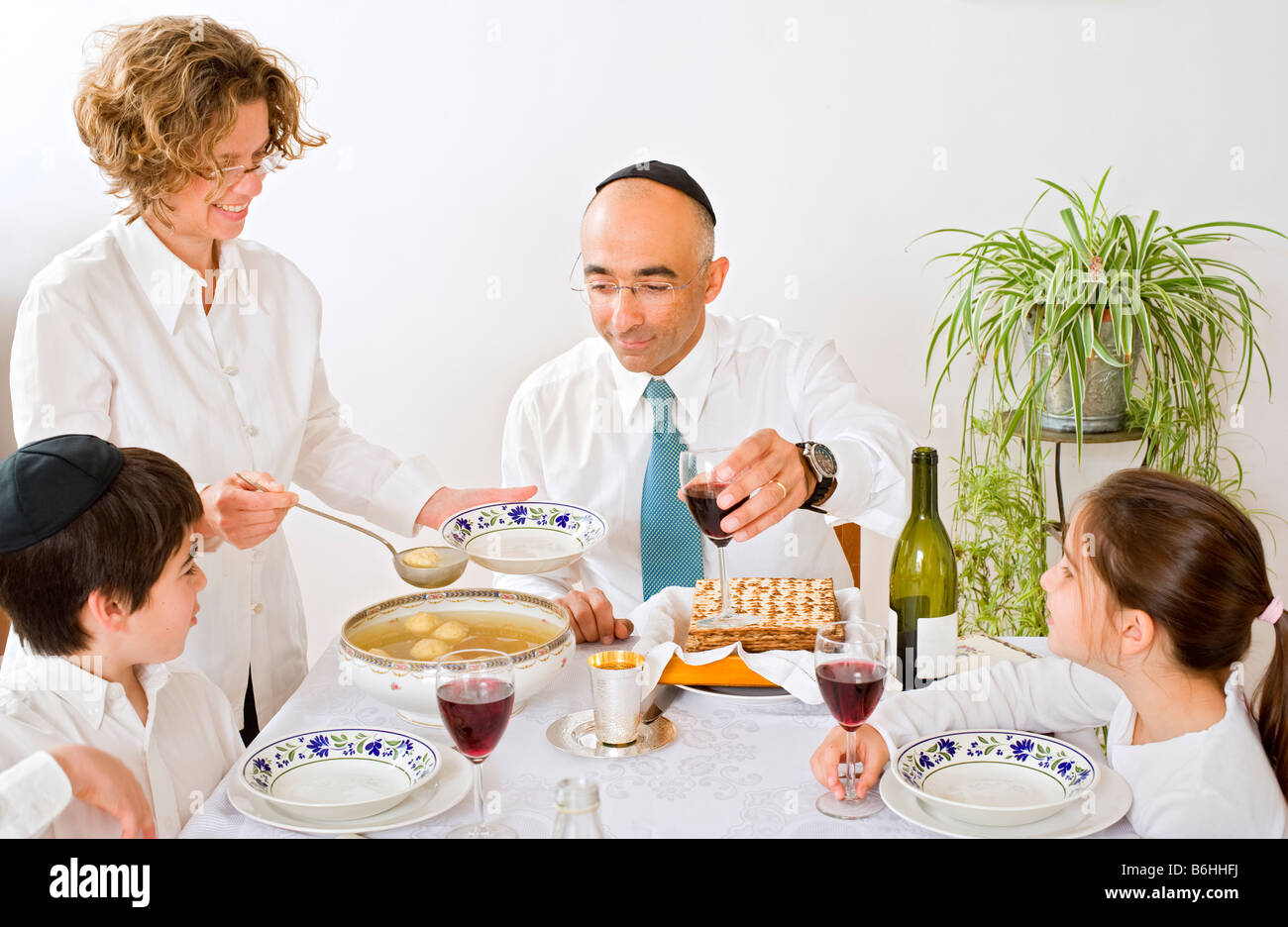 father mother son and daughter in seder celebrating passover - Stock Image